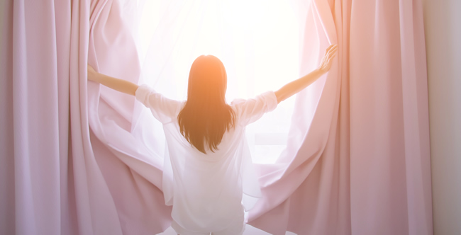 woman opening curtains in her room